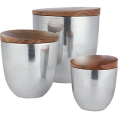 Shop aluminum canisters.   Lustrous hand-casted aluminum gets down-to-earth with an acacia wood lid, known for its distinct grain and varied colors.  Three sizes stylishly stash coffee, tea, dog treats and people treats.