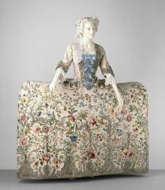 """Mantua  Place of origin: England, Great Britain (probably, made)  Date: 1740-1745 (made)  Materials and Techniques: Embroidered silk with coloured silk and silver thread  Museum number: T.260&A-1969 """"Seven panels of ivory-ribbed silk make up the petticoat. The robings, sleeve cuffs and skirt of the mantua are embroidered in the same design, but were modified to fit their exact proportions."""""""
