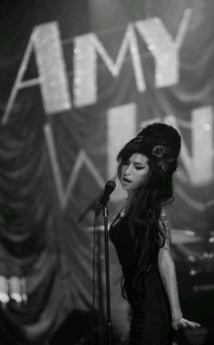 Amy Winehouse | singer | perform | tragic loss from drug addiction | rehab | 27 Club | talent artist, singer and musician | black white photography | on stage | performer | gig | beehive | concert