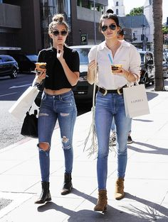 Gigi Hadid is wearing a black short sleeve crop top with blue distressed skinny jeans, black boots, sunglasses and a black crossbody bag. Kendall Jenner is wearing a white button-up with high-waisted blue jeans, suede brown ankle boots, black belt and a white fringe crossbody bag.
