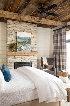 A country cabin bedroom with plaid drapes boasts a stone fireplace with a wood floating mantel displaying wall art under plank ceiling and beams.