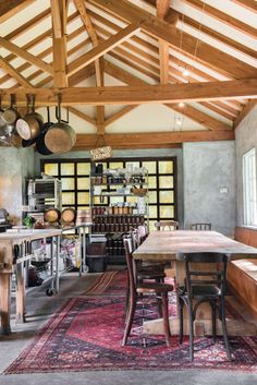 Inside the Kurtwood Farms cookhouse, industrial restaurant equipment contrasts with warm antiques: a Douglas fir dining table, Thonet chairs, and Pakistani rugs.