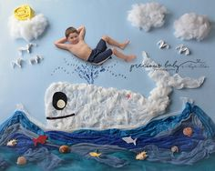A fun floor scene with a kid! A five year old boy relaxing and smiling on top of a spray of water from a whale spouting. creative unique shorts summer fun seagulls fish shells ocean waves cute hilarious funny sweet Baby ImaginArt by Angela Forker Precious Baby Photography Fort Wayne New Haven Indiana