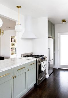 I love the pale green cabinets and gold fixtures!