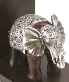 A proud pair of highly decorated elephant bookends in solid dark wood with intricate aluminium detailing.