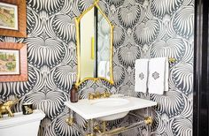 """Stunning geometric palm tree frond print gray and white wallpaper in this bathroom. Love the gold tree branch framed mirror, and the brass and acrylic bar and pipe accents below. Such a fun and fresh modern twist on a classic palette of white gold and gray. Read more on our Style Guide, """"Inside Sue De Chiara's Gorgeous Connecticut Home That's Both Totally Traditional and Full-On Fun!"""""""