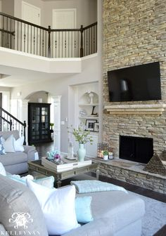 Kelley Nan: Cool Tone Spring Ready Living Room Tour- Two story neutral living room with two story windows in family room | Versatile Gray by Sherwin Williams | Dark hardwood floors in Nottaway Hickory Weathered Saddle | Gray sectional sofa | built-ins on either side of stacked stone fireplace