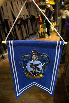 "Wizarding World Harry Potter Banner House Crest Ravenclaw NEW The Banner is made of Felt and Cotton and measures 14"" inches wide x 18"" inches long. The Hanging Rod and Rope are included. This banner features an embroidered, full-color house crest appliquéd on blue fabric. Fabric is cut in a swallowtail and trimmed in white. CONDITION: NEW with TagsHand Selected from the Wizarding World Gift Shops at Universal Orlando. Items are hand inspected to ensure you and your loved ones receive the ..."
