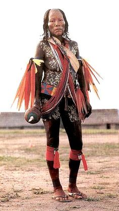 Woman decorated with an artefact made from macaw and parrot feathers and dyed cotton, carrying a gourd rattle she is about to use in a dance. Photo: Gustaaf Verswijver, 1991.
