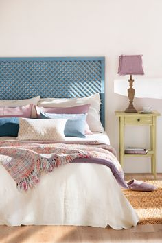 Cama con cabecero de madera pintado en azul y mesita pintada de verde. Ropa y pantalla de lámpara rosada (00425926)