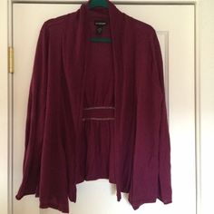 Lane Bryant cardigan Very pretty color. It's a raspberry/purple color. Full length sleeves. It's open in the front. It's drapey in the front. The back is slightly elasticized. It's very soft. It has two very tiny holes under the arm. They aren't noticeable. 50% acrylic and 50% merino wool. Lane Bryant Sweaters Cardigans