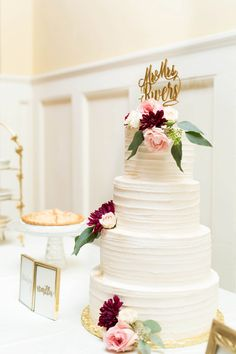Four tier white wedding cake, maroon and light pink flowers, gold customized cake topper, vanilla // Reid & Brittany Photography
