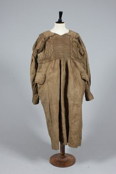 A farmer's smock, (probably Herefordshire) circa 1900, of brown drabbet with dark brown smocking, buttoned collar edges