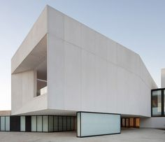 Visitors enter a theatre in Huelva, Spain, below a bulky concrete cafe that rests upon backlit glass walls.