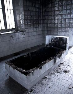 Blackened burnt bathtub in abandoned asylum