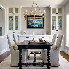 Gorgeous, traditional dining room with built-in sideboard, glass cabinets for china, a stained wooden dining table, linen slipcovered chairs and a trellis rug | Marianne Simon Design