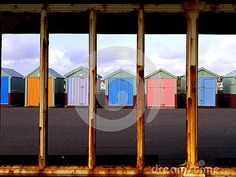 Colourful beach huts seen through structure in Hove, UK.