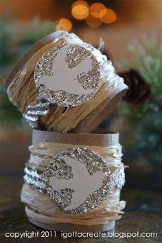 DIY - Make your own Christmas napkin rings out of: Paper towel rolls, aluminum foil, and raffia.