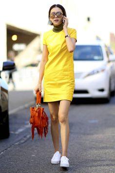 Lookée en baskets avec une robe courte en cuir jaune
