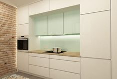 cuisine moderne et élégante avec des armoires blanches et en vert menthe et un papier peint aspect brique
