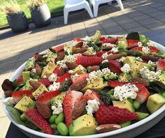 Lækker sommersalat med friske asparges, avokado, edamame bønner, feta, jordbær, saltmandler og chiadrys.