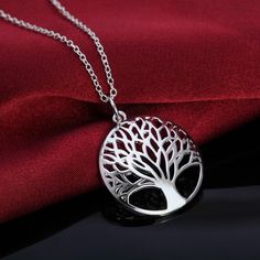 Silver plated tree of life pendant necklace on a 30 inch silver plated chain. Tree of life pendant is one inch in diameter.