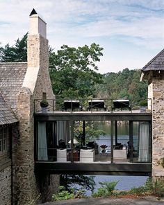 lake house with stone exterior and glass skyway | white slipcovered sofa and chair | brass mirrored top coffee table | loungers | brown striped outdoor pillows | lake house design ideas