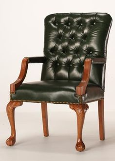 Lowell tufted leather dining chair with arms and curved legs.