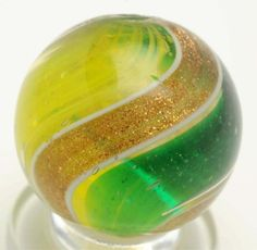"""Ribbon Lutz Swirl Marble. Price realized $90 This ribbon is unusual. One side of ribbon is translucent green and the other side is yellow. Nice, wide, full lutz banding. This marble has been buffed with pontils still intact. Very minor damage is still present. Condition (Buffed). Size 3/4"""" Dia."""