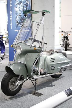 1954 Honda Juno K. Japan. Honda's first scooter featured the first electric start, first turn signal lights, a full windscreen with a tilt-back sun-shade and also the first scooter with fiber-reinforced plastic body construction.