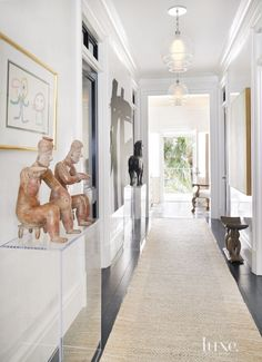 The entry hall also serves as a gallery space to show off many works of art. A wooden horse from the Tang Dynasty stands before a black-and-white painting by EEK from Mecox, while an aboriginal totem sourced from an art fair leans near the door in the distance.