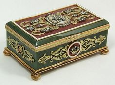 An exquisite and stunning Faberge hinged box constructed of translucent nephrite jade with spinach mottling with 14k yellow gold frame, feet and appliques. Jeweled throughout with floral, crown and monogram designs over opalescent and red guilloche enamel. Set with diamonds and cabochon ruby jewels. Holds Dmitri Aleksandrov Pastukhov workmaster marks.