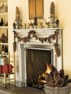Woodsy Fireplace: Brawny sugar pinecone swags anchor a mixed-cone garland above the fireplace. Make it yourself with a variable-speed drill and braided picture-hanger wire. Drill a hole in the top of each pinecone, then run the wire through to create the strand. Place inverted cones in urns to create pinecone topiaries.