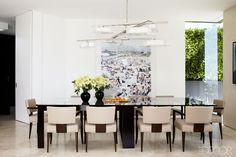 Chad Eisner Interiors - 1970s LA Art Deco Home - ELLE DECOR - The photograph in the dining area is by Massimo Vitali, and the light fixture is by PaganiStudio; the Moura Starr table is surrounded by Powell & Bonnell armchairs upholstered in a Jerry Pair leather.