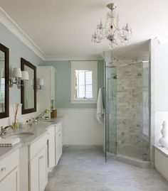 Gorgeous master bathroom design with spa blue walls paint color, chair rail with subway tiles backsplash, corner frameless glass shower, calcutta marble tiles shower surround, white carrara marble tiles floor, white double bathroom cabinets vanity with marble counter tops, double sinks, espresso rectangular bathroom mirrors.