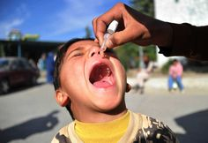 The 24 Most Inspiring Photos of 2012 // An Afghan health worker administers a polio vaccination to a boy on the second day of a vaccination campaign in the city of Jalalabad on November 20, 2012.