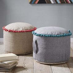 NEW! Made of handwoven fabric and lined with a bright ring of contrasting pom poms, this pouf's round shape makes it easy to fit in front of a sofa or chair. Plus, a sturdy handle allows you to easily transport it from room to room.