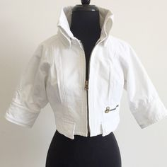 """A/X Armani Exchange White Cropped Denim Jacket M White jacket from Armani Exchange features a standup collar, cropped body, elbow length raglan/dolman sleeves, zip front, flap faux pockets & single zipper pocket. Cuff sleeves with snap closures. Pleating detail at chest, back. Fully lined.   • size M • 36"""" bust   15.5"""" sleeves from neck   15.5"""" length • 100% cotton • gently worn a few times  • ***please note there is a faint pink mark by the rt shoulder, not very noticeable. Also a pink mark…"""
