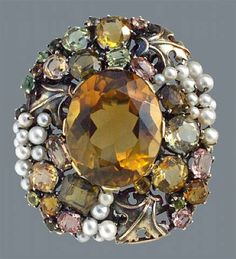 Dorrie Nossiter. Arts and Crafts brooch. Silver, gold, citrine, tourmaline and pearl, c. 1930. H: 4.3 cm, (1.69 in), W: 3.9 cm (1.54 in). Fitted case. Sold by Tadema Gallery.