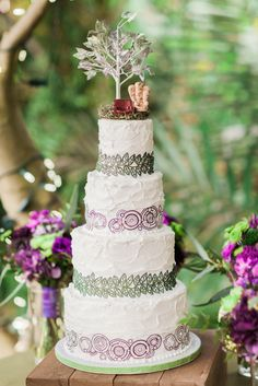 """Our wedding cake had alternating edible lace ribbons of green vines to go with our natural theme and purple gallifreyan writing.  You can also see our cake topper of the chairs from the Disney Pixar film """"Up"""" and the white tree of Gondor.  nerdy wedding; disney wedding; disney cake topper; wedding cake table decoration; Our cake was created by CC's Sweet Sensations.  Photography by Dan & Erin PhotoCinema."""