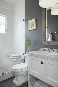 Bathroom with white vanity, dark grey tile, grey walls, and framed mirror.