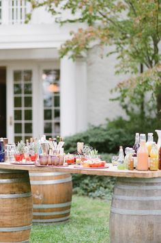 Cocktail bar on wooden barrels for a vineyard wedding reception. Cocktail bar by The Catering Outfit, image by Kristen Lynne Photography.