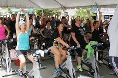 Pedal for Pirates Charities participants stretch during their hour session on Federal Street.