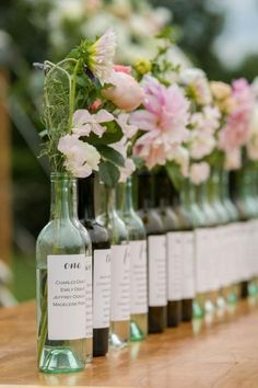 Wine corks are the usual go-to for vineyard wedding seating charts, but we think we love using wine bottles even more. Each bottle's label features the guest names for one table, while also being used as a vase. @myweddingdotcom #WeddingIdeasUnique