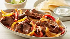 These oven-baked beef fajitas are a quick and easy spin on the classic version. The sliced beef, onions and peppers are seasoned and roasted together on a sheet pan, making this a great weeknight dinner with little cleanup.