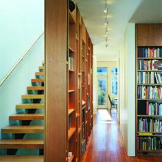 A two-story bookcase of wood and glass acts as a room divider and light chimney, bringing sunlight into the parlor of a remodeled San Francisco Victorian.