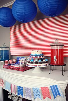 Great July 4th table. I want a white cake stand like that- one you can weave ribbon around to change colors for the occasion.  I like the clear drink containers too with red & blue drinks.
