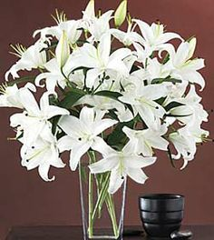 12 pieces white lilies arranged in a glass vase, this design is well suited for delivery to the residence, as well as to the funeral home or service