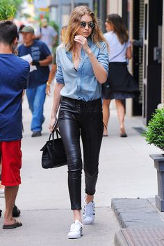 Gigi Hadid wearing black leather skinny pants, a chambray button-down shirt, black and white shell toe Adidas, and a Versace top-handle tote