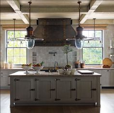 That is one crazy big range hood! I love the lamps but maybe they are too big for this space. They draw the eye to high and you completely miss those gorgeous doors on the island...